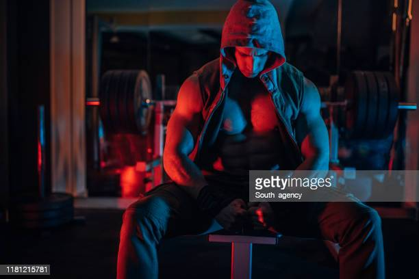 fit man sitting in dark gym - handsome bodybuilders stock pictures, royalty-free photos & images