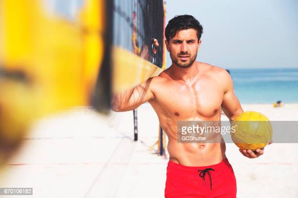 Fit man standing holding the volleyball net at the beach