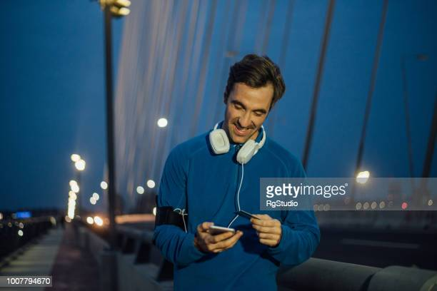 fit man with headphones shopping online - charging sports stock pictures, royalty-free photos & images