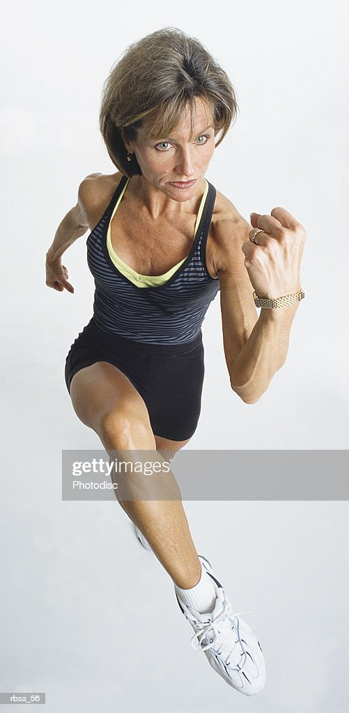 fit mature adult caucasian female wearing a tank top and exercise shorts and tennis shoes is running forward as she focuses ahead and clenches her fists in concentration : Foto de stock