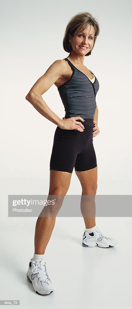 fit mature adult female caucasian wearing a tank top and exercise shorts with tennis shoes standing sidelong with legs apart and hands on hips looking at camera with a confident expression : Foto de stock