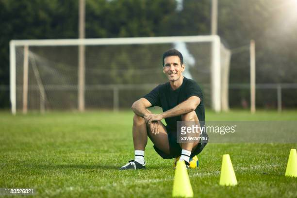 fit mature male footballer waiting for start of practice - coach stock pictures, royalty-free photos & images