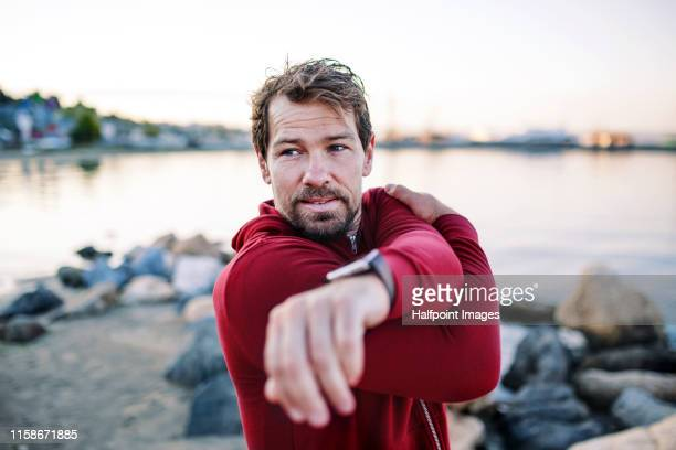 a fit mature sportsman runner doing exercise outdoors on beach, stretching. - mature men stock pictures, royalty-free photos & images