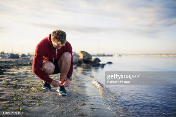 a fit mature sportsman runner tying shoelaces outdoors on beach. - tying stock pictures, royalty-free photos & images