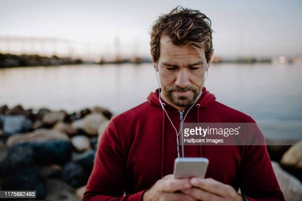 a fit mature sportsman runner with earphones standing outdoors on beach, using smartphone. - checking sports stock pictures, royalty-free photos & images