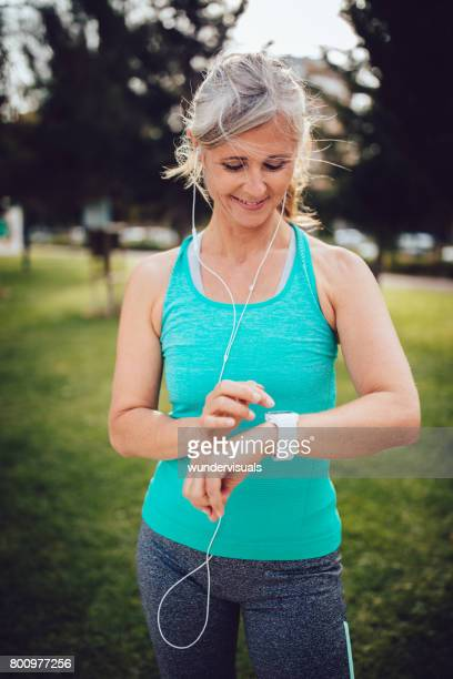 Fit mature woman runner checking her pulse on smartwatch