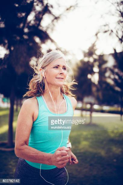 fit mature woman running in the park at sunset - sporting term stock pictures, royalty-free photos & images