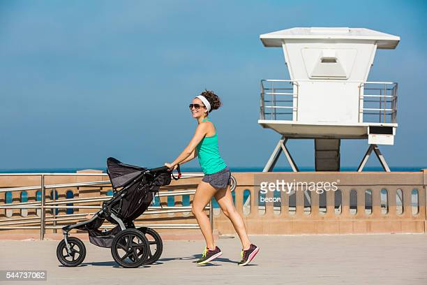 fit mom running at the beach with baby jogger - three wheeled pushchair stock pictures, royalty-free photos & images