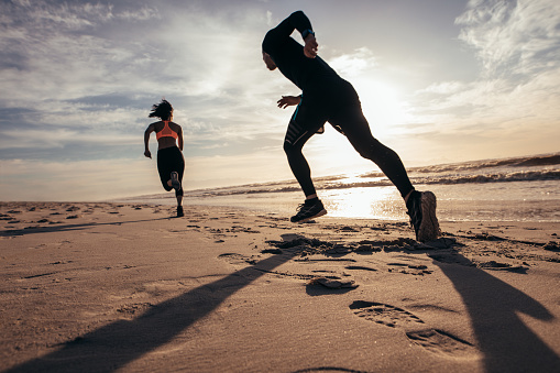 Fit people sprinting on the beach 957463426