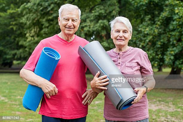 Fit senior couple holding yoga mat in the park