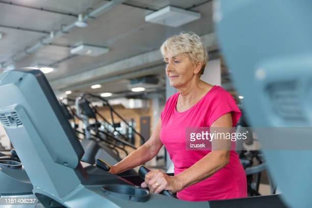 fit senior woman exercising on treadmill - drug rehab stock pictures, royalty-free photos & images
