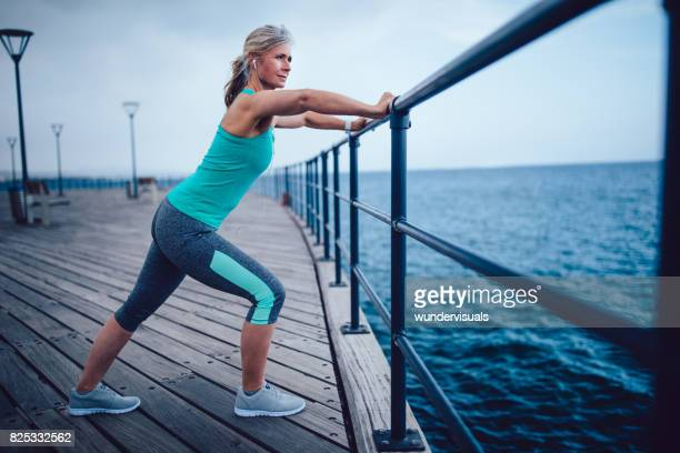 fit senior woman stretching before working out by the sea - older woman legs stock photos and pictures