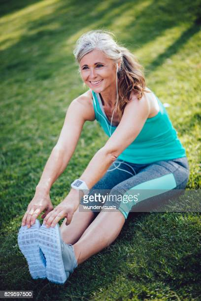 fit senior woman with smartwatch and earphones stretching before jogging - older woman legs stock photos and pictures