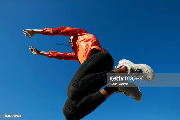 fit sportsman jumping against clear blue sky - sportswear stock pictures, royalty-free photos & images