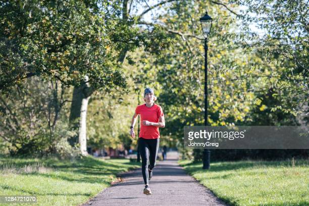 fit sportswoman in early 50s enjoying run in public park - clapham common stock pictures, royalty-free photos & images