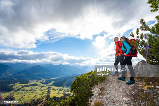 fit sporty mountaineer couple on view point in mountains - escursionismo foto e immagini stock