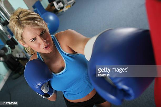 fit sporty woman puncking a boxing bax exercising in gym