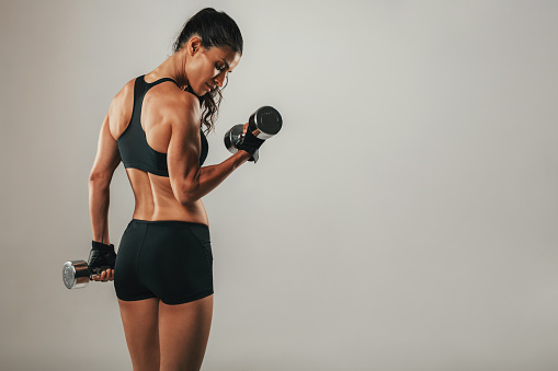 Fit strong young woman lifting weights 621586122