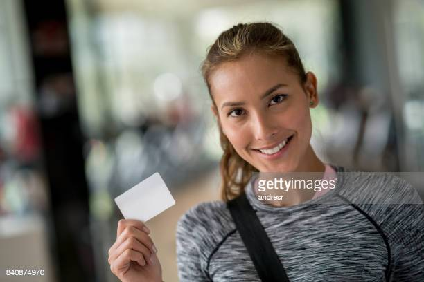 Fit woman at the gym holding a loyalty card