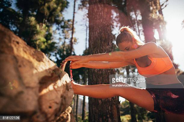 Fit woman athlete stretching leg on a nature trail run