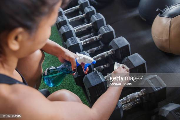 fit woman cleaning dumbbell with disinfectant spray - centro benessere struttura ricreativa foto e immagini stock