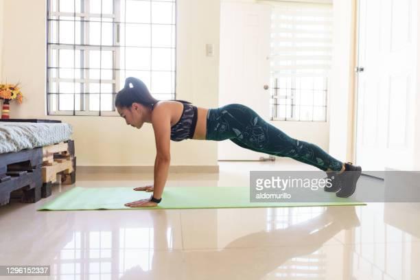 自宅で運動をしているフィット女性 - 自重トレーニング ストックフォトと画像
