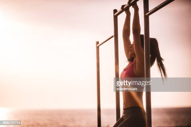 Fit woman doing pull ups at sunset by the sea