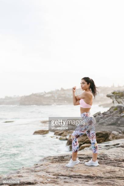 fit woman doing stretches on rocks - yoga pants stock photos and pictures