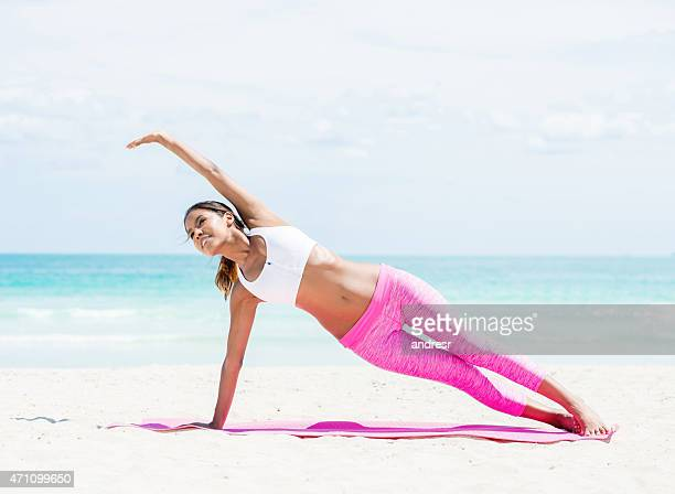 Fit woman doing yoga at the beach