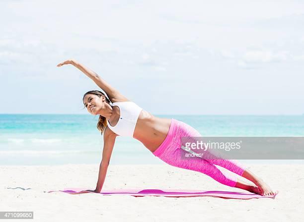 Femme Fit faire du yoga sur la plage