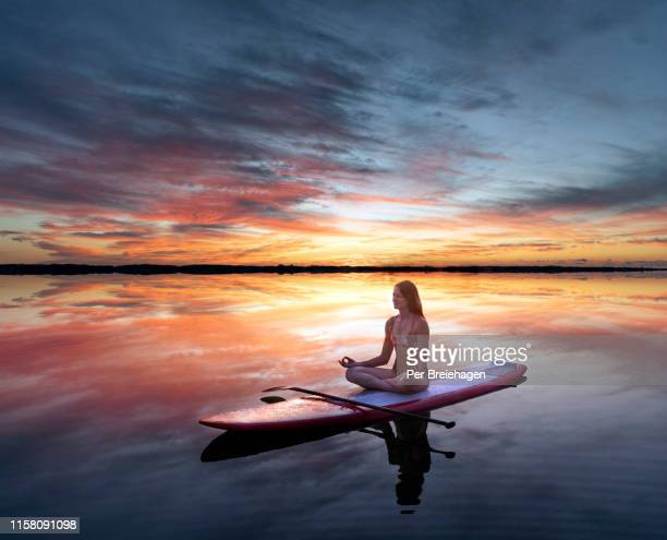 a fit woman doing yoga on a paddleboard at sunset - paddleboard stock photos and pictures