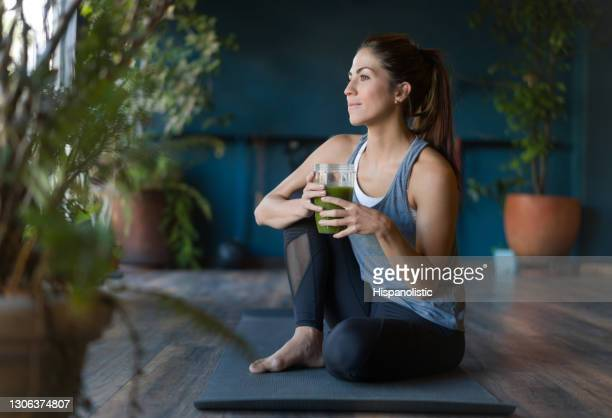 fit woman drinking a green detox smoothie at the gym - juice drink stock pictures, royalty-free photos & images