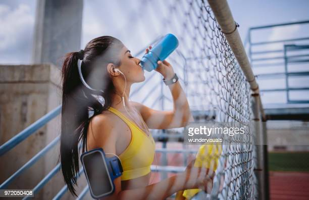 fit woman drinking water and listening to music after workout - lap body area stock photos and pictures