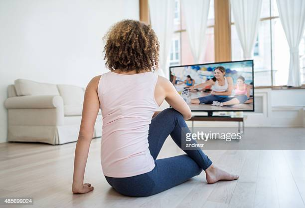 Fit woman exercising at home watching a DVD