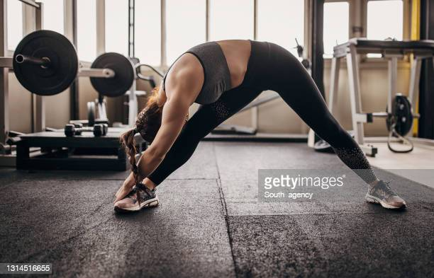 fit woman exercising in gym - warming up stock pictures, royalty-free photos & images