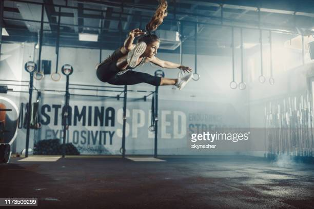 fit woman exercising jumps on cross training in a health club. - legs apart stock pictures, royalty-free photos & images