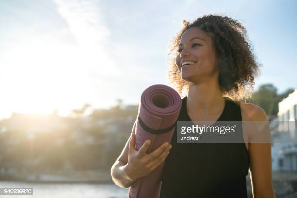 fit woman holding a yoga mat at the beach - outdoors stock pictures, royalty-free photos & images