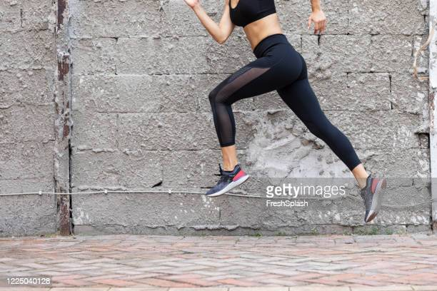 fit woman in black sportswear running outdoors - nylon stock pictures, royalty-free photos & images