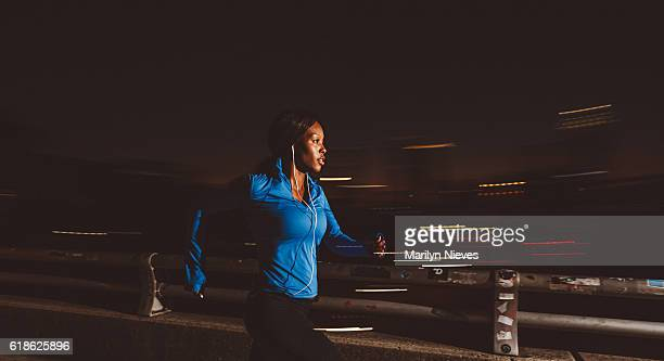 fit woman jogging at night through the city