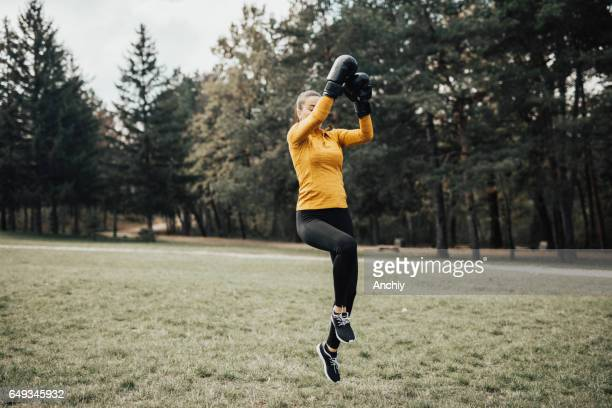 Fit woman kickboxer doing flying knee kick