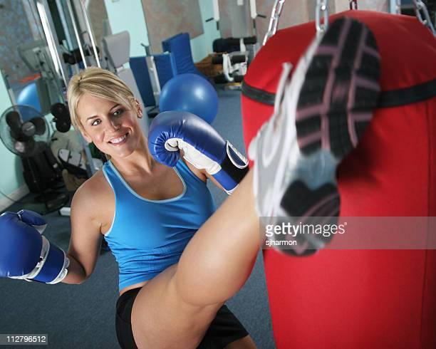 Fit woman kicking a punching bag in gym exercising