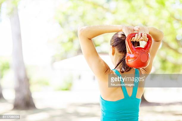 Fit Woman Lifting Kettle Bell In Park