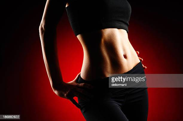fit woman on red background - waist stock pictures, royalty-free photos & images