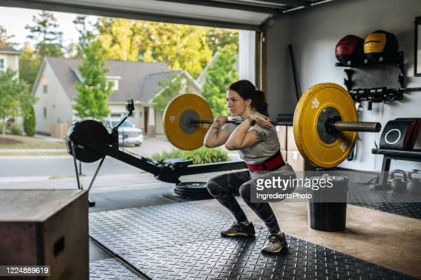 fit woman performing front squat with heavy barbell in her home garage gym during covid-19 pandemic. - gym stock pictures, royalty-free photos & images