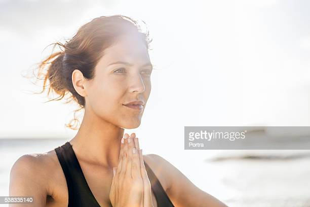 Fit woman practicing yoga at beach