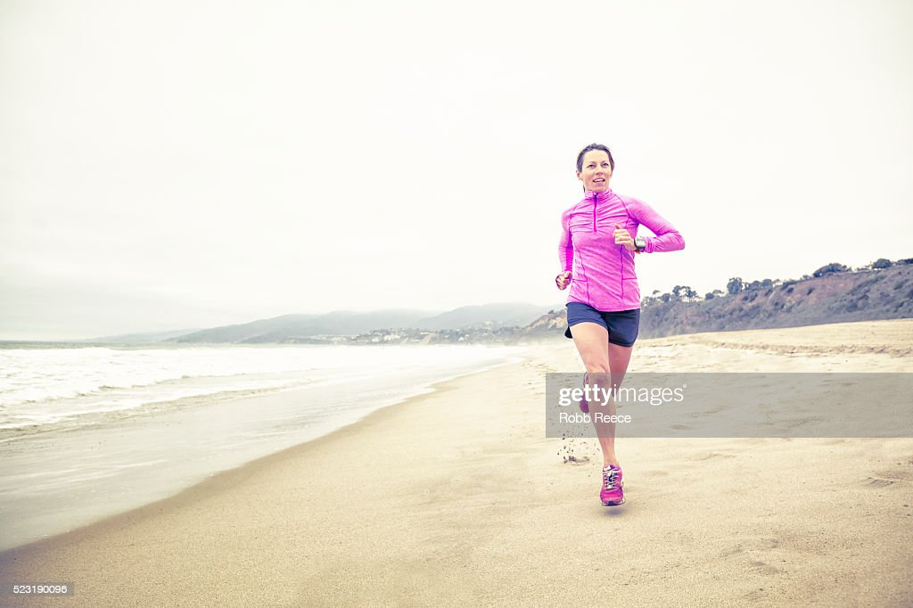 A fit woman running fast in the sand on the beach for fitness training : Stock Photo