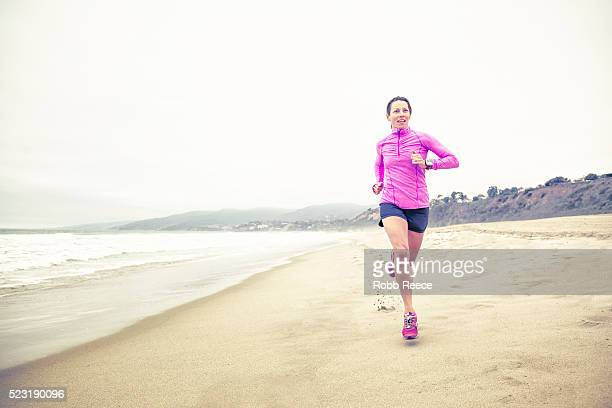 a fit woman running fast in the sand on the beach for fitness training - robb reece stockfoto's en -beelden