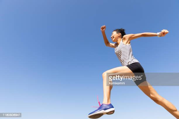 fit woman running - blue shorts stock pictures, royalty-free photos & images