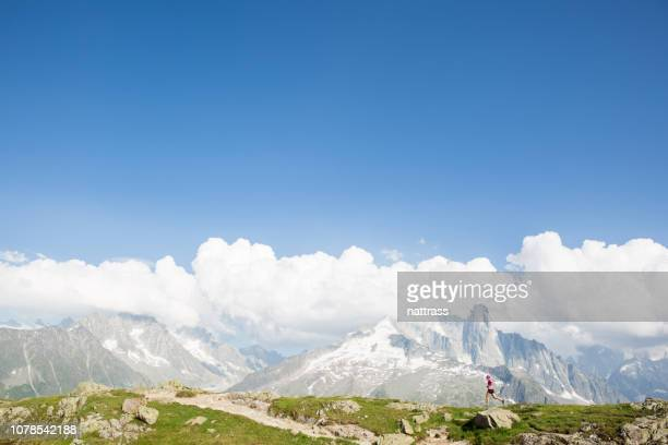 fit woman runs up a mountain path - auvergne rhône alpes stock pictures, royalty-free photos & images