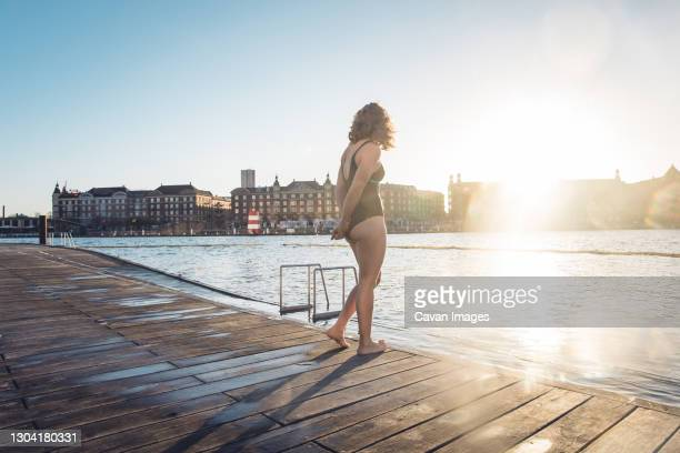 fit woman standing alone on dock before swim in copenhagen, denmark - denmark stock pictures, royalty-free photos & images